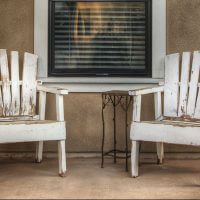Bradley Studios outside eye level view of two chairs under a window on the porch