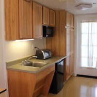 El Carrillo apartment kitchen with wood finish cabinets