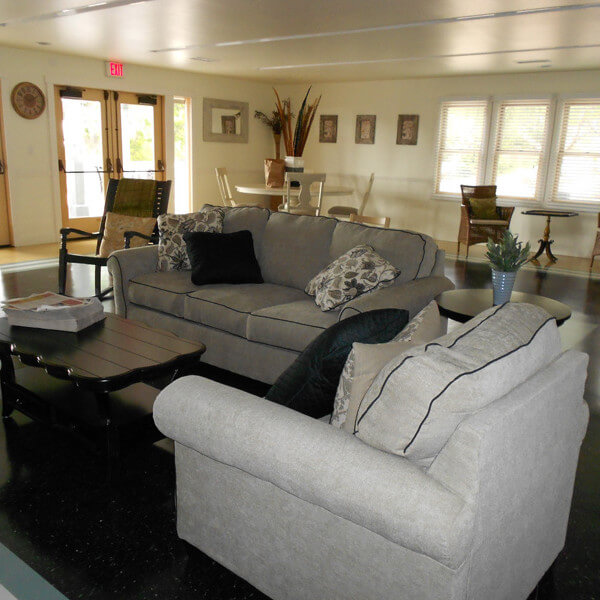 Inside of a common room with couches, tables, and chairs
