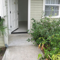 Outside view of the path leading to an open door of a unit