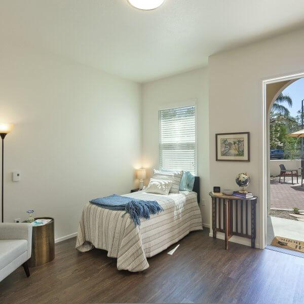 Studio bedroom with bed, chair and door