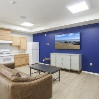 photo of community room with kitchen, tv, couch